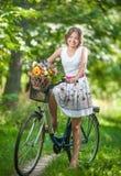 穿一件精密白色礼服的美丽的女孩获得乐趣在有自行车的公园 健康室外生活方式概念 葡萄酒风景 免版税图库摄影