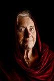 穿一件红色披肩的一名资深妇女的剧烈的画象 库存照片