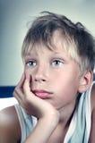 穿一件绿色汗衫的美丽的白肤金发的男孩作梦和看起来哀伤 免版税图库摄影