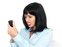 穿一件蓝色衬衣的恼怒的沮丧的少妇使用Chordless电话 库存照片