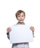 穿一件蓝色衬衣的美丽的滑稽的白肤金发的男孩拿着小空白的横幅 免版税库存图片