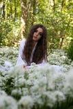 穿一件长的白色礼服的美丽的妇女坐在森林o里 免版税库存图片