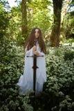 穿一件长的白色礼服的美丽的妇女拿着剑 免版税库存图片