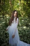 穿一件长的白色礼服的美丽的妇女站立在森林里 库存照片