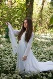 穿一件长的白色礼服的美丽的妇女站立在森林里 免版税图库摄影