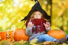 穿万圣夜服装的可爱的小女孩获得在一个南瓜补丁的乐趣在秋天天 免版税库存照片