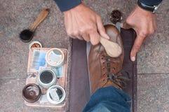 穿上鞋子在街道的亮光在棕色皮鞋 免版税库存照片