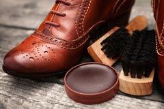 穿上鞋子奶油、刷子和棕色皮鞋 库存图片