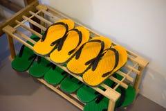 穿上鞋子有黄色和绿色橡胶凉鞋或拖鞋的机架 图库摄影