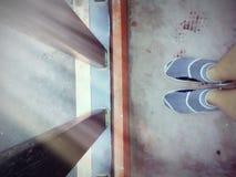 穿上鞋子站立在阳台前面的人 免版税图库摄影