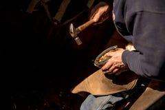 穿上鞋子马的钉马掌铁匠 免版税库存图片