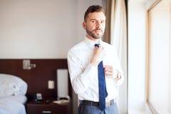 穿上他的领带的商人 图库摄影
