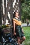 穿与学院看起来的美丽的女孩好衣服获得乐趣在有运载一个美丽的篮子的自行车的公园 葡萄酒风景 免版税图库摄影
