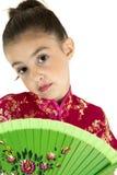 穿中国礼服的美丽的女孩拿着爱好者 免版税库存照片