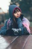 穿五颜六色的围巾和夹克有盖帽的冷气候的时兴的女性摄影师 库存图片