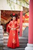 穿传统中国新娘礼服的亚裔美丽的年轻女人, 免版税库存图片