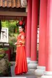 穿传统中国新娘礼服的亚裔美丽的年轻女人 免版税库存照片