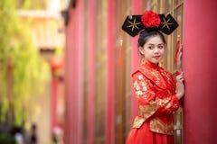 穿传统中国新娘礼服的亚裔美丽的年轻女人 免版税库存图片