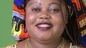 穿传统衣物的超重美丽的非洲妇女反对绿色背景 股票录像