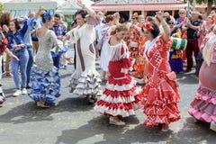 穿传统Sevillana礼服和公平地跳舞Sevillana的妇女在塞维利亚4月 库存图片