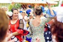 穿传统Sevillana礼服和公平地跳舞Sevillana的妇女在塞维利亚4月 库存照片