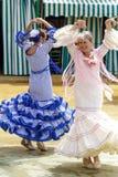 穿传统Sevillana礼服和公平地跳舞Sevillana的妇女在塞维利亚4月 免版税库存图片