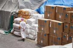 穿传统阿拉伯服装的一个未认出的人通过口岸仓库走 免版税库存照片
