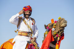 穿传统Rajasthani礼服的骆驼和印地安人参加先生 作为沙漠节日一部分的沙漠比赛在Jaisalme 免版税图库摄影