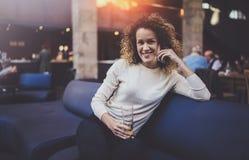穿便衣和使用手机的英俊的女孩在她的休息时间在咖啡店 Bokeh和火光 库存照片