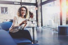 穿便衣和使用手机的英俊的女孩在她的休息时间在咖啡店 Bokeh和火光 图库摄影