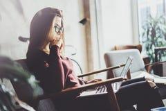 穿便衣和工作在coworking的办公室的可爱的年轻女实业家 使用当代机动性的女性 免版税图库摄影