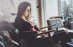 穿便衣和工作在coworking的办公室的可爱的年轻女实业家 使用当代机动性的女性 库存图片