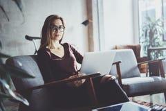 穿便衣和工作在coworking的办公室的可爱的年轻女实业家 使用当代机动性的女性 免版税库存图片
