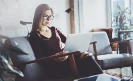 穿便衣和工作在coworking的办公室的可爱的年轻女实业家 使用当代机动性的女性 免版税库存照片