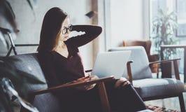 穿便衣和工作在coworking的办公室的可爱的年轻女实业家 使用当代机动性的女性 库存照片