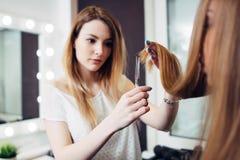 穿便衣的年轻俏丽的美发师拿着长的头发子线在整理在秀丽的手指之间的末端 免版税库存照片