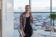 穿偶然明亮的衬衣的少妇站立在轻的宽广的办公室,她的工作场所,在工作天准备,微笑 免版税库存图片