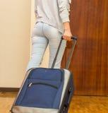 穿偶然裤子的妇女的腿走往拉扯蓝色手提箱,旅舍客人概念的门 图库摄影