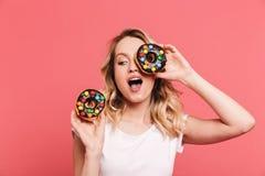 穿偶然T恤杉的欢悦白肤金发的妇女20s画象微笑,当拿着鲜美甜油炸圈饼时 免版税库存照片