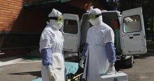 穿充分的埃博拉病毒保护制服Â的两位无法认出的医生或护士站立近的救护车汽车和 影视素材