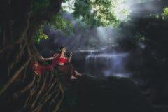 穿典型的泰国礼服的妇女在瀑布 库存图片