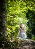 穿典雅的白色礼服的可爱的小姐享受神圣光射线在她的面孔的在被迷惑的森林。相当白肤金发 库存照片