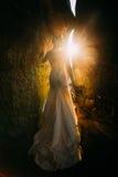 穿典雅的白色礼服的美丽的少妇剪影站立在与黄色日落的两个岩石之间发出光线 免版税库存图片