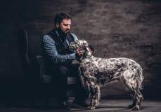 穿典雅的衣裳的有胡子的猎人坐有他的白英国塞特种猎狗的一个沙发 库存照片