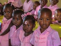 穿制服在桃红色幼儿园老师在农村海地 免版税库存照片