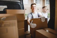 穿制服的两名年轻英俊的工作者在搬运车箱子旁边充分站立 议院移动,搬家工人服务 免版税库存照片