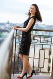 穿古典黑礼服的可爱的年轻美丽的女孩摆在豪华大厦阳台  免版税库存照片