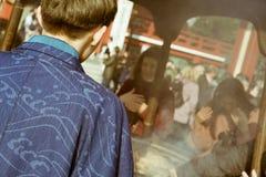 穿和服的传统日本人祈祷由在著名佛教寺庙Senso籍的熏香台在浅草,东京,亚帕 免版税库存图片