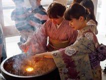 穿和服的年轻女人点燃香火棍子,京都,日本 免版税库存照片