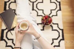 穿困厄的牛仔裤的一个少妇在家坐在地毯地毯的木地板和拿着一杯咖啡在手上 aromaticity 免版税库存照片